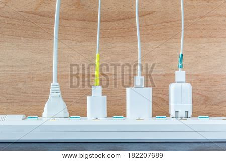 Variety electricity cables from charging station with wooden background energy supply concept.