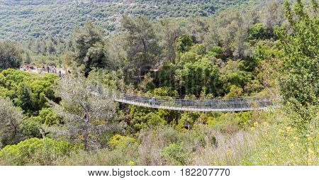 Visitors to the national park near the city Nesher cross the suspension bridge over the river Katya Israel