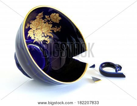 Broken porcelain cobalt blue cup on white