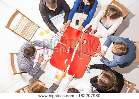 Team sitting behind desk, checking reports, talking, collecting puzzles together. Top View. The business concept of collaboration, team work, meeting