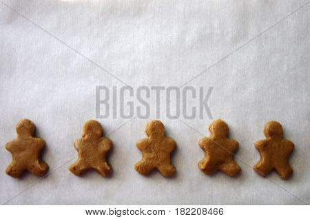 Raw dough Gingerbread men  cookie shapes on white