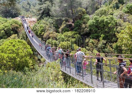 Nesher Israel - April 11 2017 : Visitors to the national park near the city Nesher cross the suspension bridge over the river Katya Israel