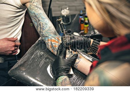 Focus on top view of close up equipment which keeping female artist. She making tattoo picture on arm of male