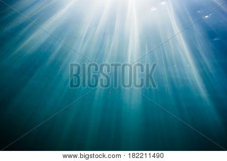 Sun rays in underwater. Ocean pattern in water. Ocean texture