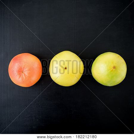 Grapefruit and sweetie on black background. Flat lay, top view. Fruit colorful background