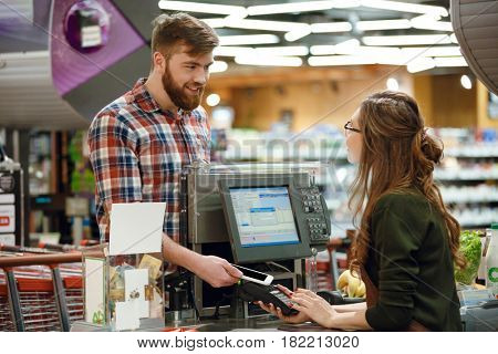 Image of cashier lady on workspace in supermarket shop create payment with mobile phone app.