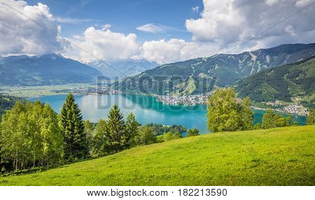 Panoramic view of beautiful scenery in the Alps with clear lake and green meadows full of blooming flowers on a sunny day with blue sky and clouds in springtime Zell am See Salzburger Land Austria