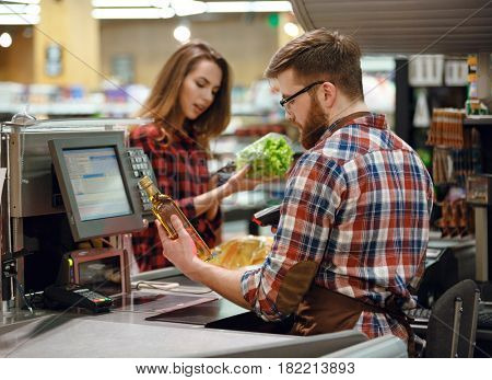 Image of concentrated cashier man on workspace in supermarket shop. Looking aside.