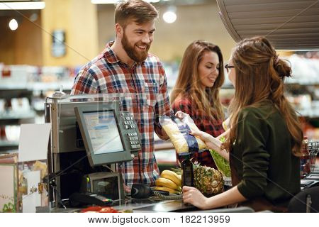 Image of cheerful young man standing in supermarket shop near cashier's desk. Looking aside.