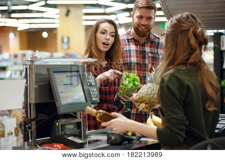 Picture of concentrated young loving couple standing in supermarket shop near cashier's desk. Looking aside.