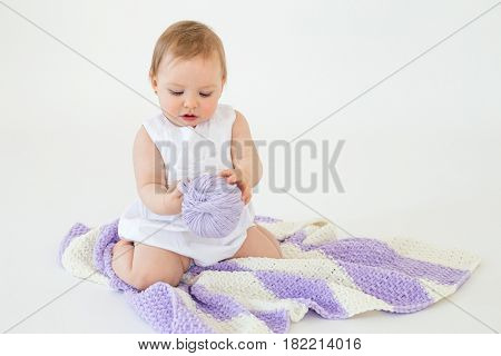 Photo of little baby girl sitting on floor with plaid isolated over white background playing with threads ball. Looking aside.