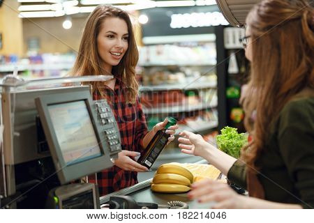 Image of smiling young lady standing in supermarket shop near cashier's desk. Looking aside.