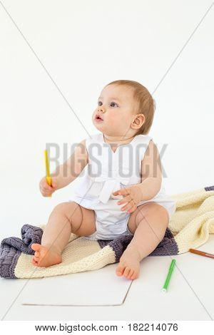 Picture of cute baby girl sitting on floor on plaid holding markers isolated over white background. Looking aside.