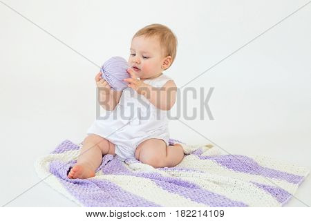 Picture of cute little baby girl sitting on floor with plaid isolated over white background playing with threads ball. Looking aside.