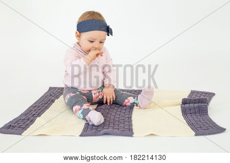 Picture of pretty girl sitting on floor with plaid isolated over white background. Looking aside.