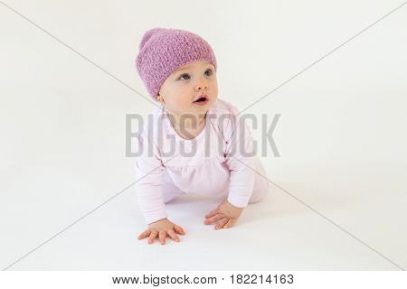 Picture of cute little baby girl wearing hat sitting on floor isolated over white background. Looking aside.