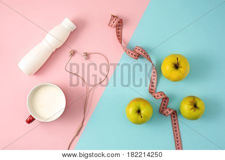 The green apple and bottle of yogurt with measure tape. Concept of diet and healthy lifestile