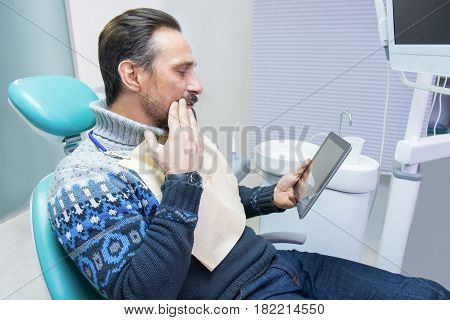 Adult man in dental office. Guy with toothache holding tablet. Precise diagnosis and effective treatment.