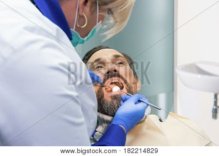Female dentist working. Stomatologist checking teeth. Professionals always ready to help.
