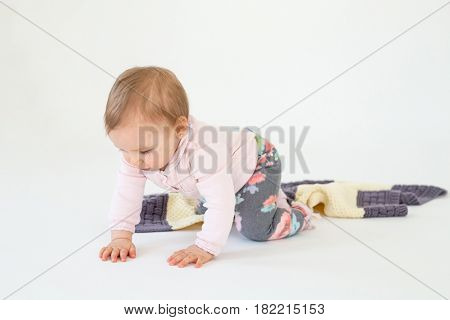 Picture of pretty baby girl sitting on floor with plaid isolated over white background. Looking aside.