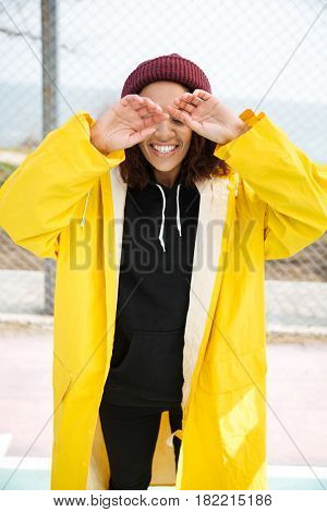Photo of happy african young lady walking outdoors dressed in yellow raincoat. Looking aside.