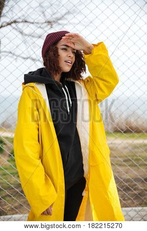 Image of serious african young lady walking outdoors dressed in yellow raincoat. Looking aside.