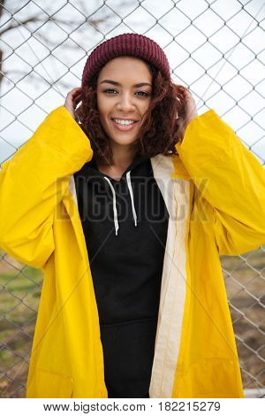 Picture of smiling african young lady walking outdoors dressed in yellow raincoat. Looking at camera.