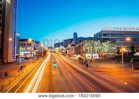 Minsk, Belarus - April 3, 2017: Evening Night Traffic Near Cathedral of Saints Peter and Paul and Bas-relief of the Soviet era on old facade building On Illuminated Nemiga Street In Minsk, Belarus