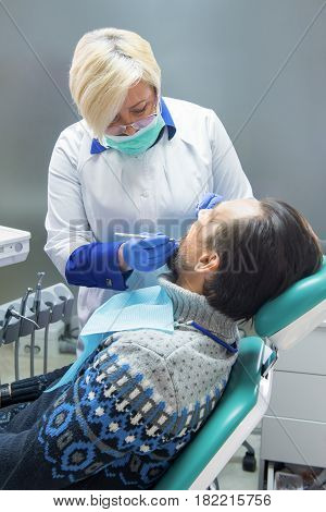 Female dental doctor working. Stomatologist and patient in chair. Most experienced dentist.