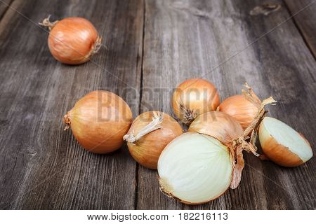 Fresh fruit onions on a wooden background.