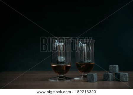 Grey stones cubes for cooling whiskey and glases tulip on dark wooden background