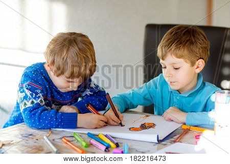 Two little kids boys at school making homework, painting a story with colorful pens. Little children writing with pencils, indoors. Elementary school and education, imagine fantasy concept.