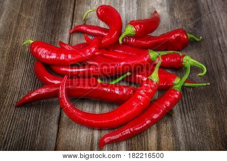 Red hot peppers on a wooden background.