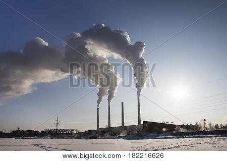Smoking chimney of industrial buildings complex. Day