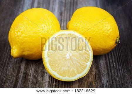 Fresh fruit lemons on the a wooden background.