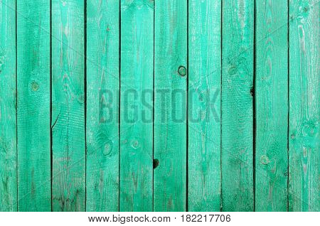 Fragment of green painted rough wooden boards background