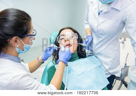 Dentists working with patient. Lady in safety glasses. Qualified dental specialists.