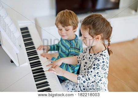 Two little kids girl and boy playing piano in living room or music school. Preschool children having fun with learning to play music instrument. Education, skills concept.
