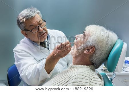 Elderly man at the dentist. Stomatologist is examining patient. High experience in medicine.