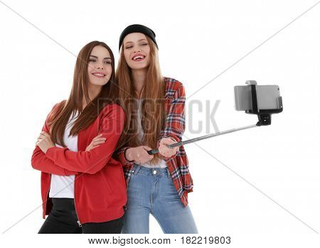 Happy young women taking selfie on white background