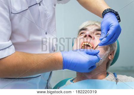 Senior patient at the dentist. Hands of medic in gloves.