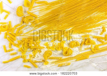 Various types of pasta on a white marble table with flour, shot from above