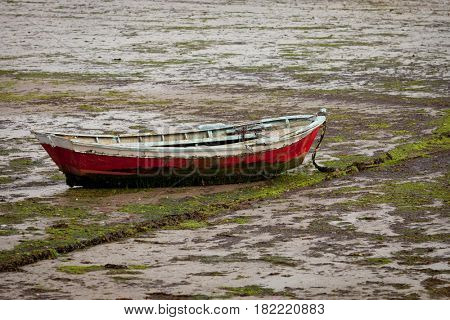 Little fishing boat stranded on the wet sand by low tide