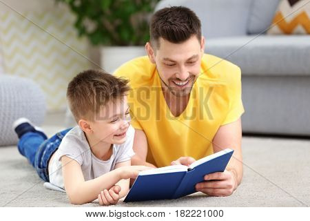 Dad and son reading interesting book at home