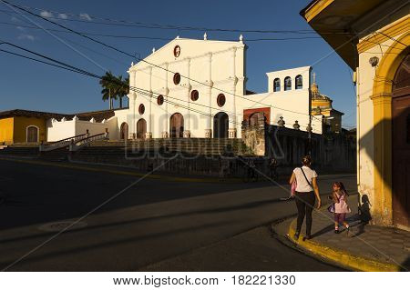 Granada Nicaragua - April 3 2014: Mother and daughter in a street of the colonial city of Granada in Nicaragua with the San Francisco Convent on the background at sunset
