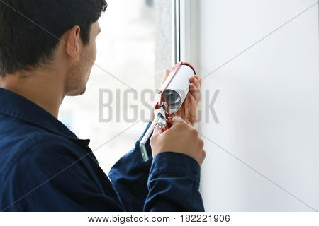 Young worker sealing joints of office window