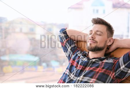 Happy young man resting in armchair near big window