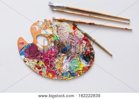 Art palette with colorful paint strokes and paintbrushes on white isolated background, top view, flat lay, object