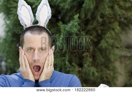 Surprised man with bunny ears on his head.