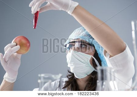 Scientific Research Concept and Ideas.Female Laboratory Staff Conducting Experiment with GMO and Apple Specimen. Horizontal Image